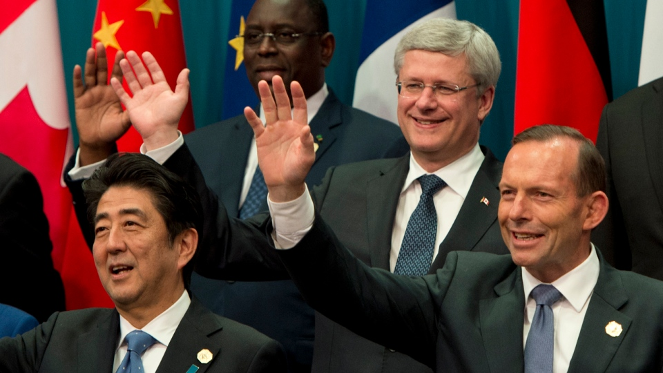 Prime Minister Stephen Harper, Senegal President Macky Sall(back left), Japanese Prime Minister Shinzo Abe and Australian Prime Minister Tony Abbott (front right) wave during the family photo at the G20 Summit in Brisbane, Australia Saturday Nov. 15, 2014. (Adrian Wyld / THE CANADIAN PRESS)