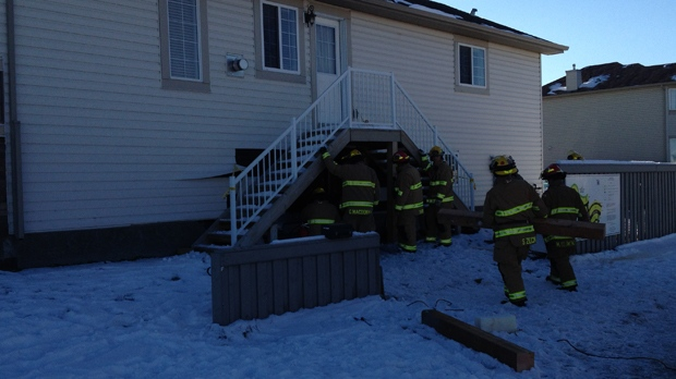 Members of the Calgary Fire Department assess the damage to a Martindale home after a vehicle crashed through an exterior wall