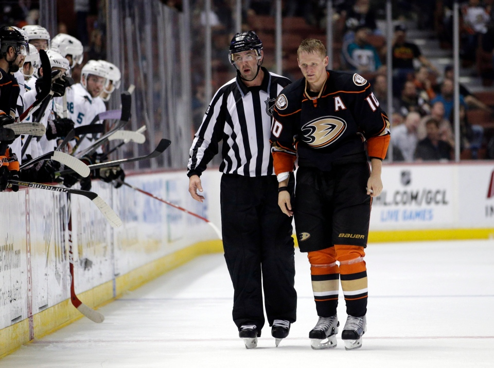 Anaheim Ducks' Corey Perry, right, is escorted off the ice by linesman Brian Mach after receiving a penalty for misconduct during the third period of an NHL hockey game against the San Jose Sharks, Sunday, Oct. 26, 2014, in Anaheim, Calif. The Sharks won 4-1. (AP Photo/Jae C. Hong)