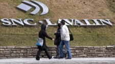 Pedestrians walk past the offices of SNC Lavalin are seen Monday, March 26, 2012 in Montreal. (Ryan Remiorz / THE CANADIAN PRESS)