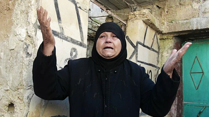 A Syrian woman reacts outside her house which attacked by Syrian government forces shelling at Sarmeen town in Idlib province, northern Syria on Saturday, March 24, 2012.  (Edlib News Network ENN)