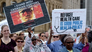 Health care providers and supporters hold a rally to protest federal cuts to refugee care on Parliament Hill in Ottawa, Monday, June 16, 2014. (Sean Kilpatrick / THE CANADIAN PRESS)