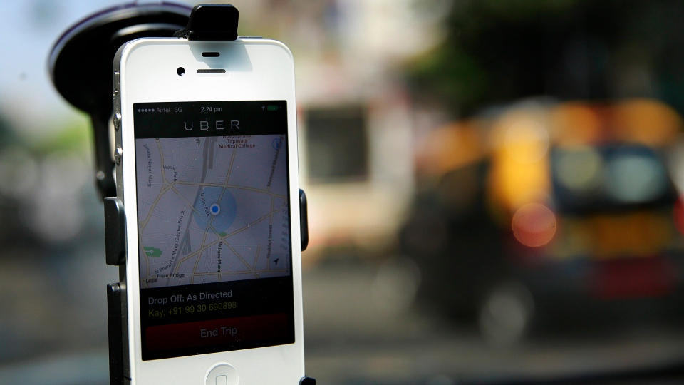 In this 2014 photo, a smartphone is mounted on the glass of an Uber car. (AP / Rafiq Maqbool)