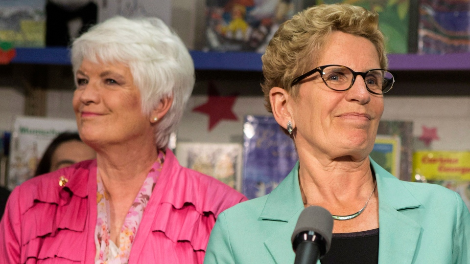 Ontario Premier Kathleen Wynne (right) stands with Education Minister Liz Sandals as she addresses the media at Westwood Public School in Guelph, Ontario on Wednesday, May 14, 2014. (Chris Young / THE CANADIAN PRESS)
