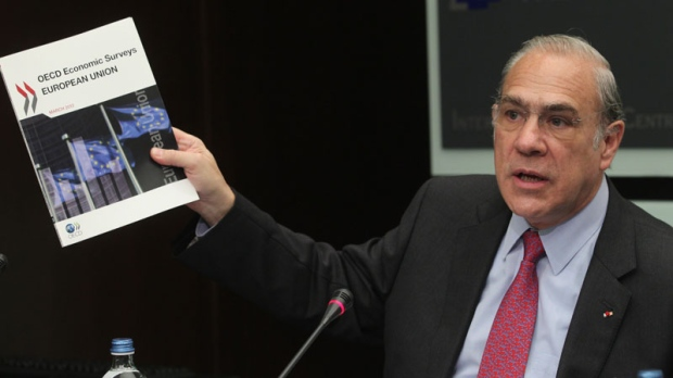 Angel Gurria, the head of the Paris-based international development body, OECD, shows a survey to the media in Brussels, Tuesday, March 27, 2012.  (AP / Yves Logghe)