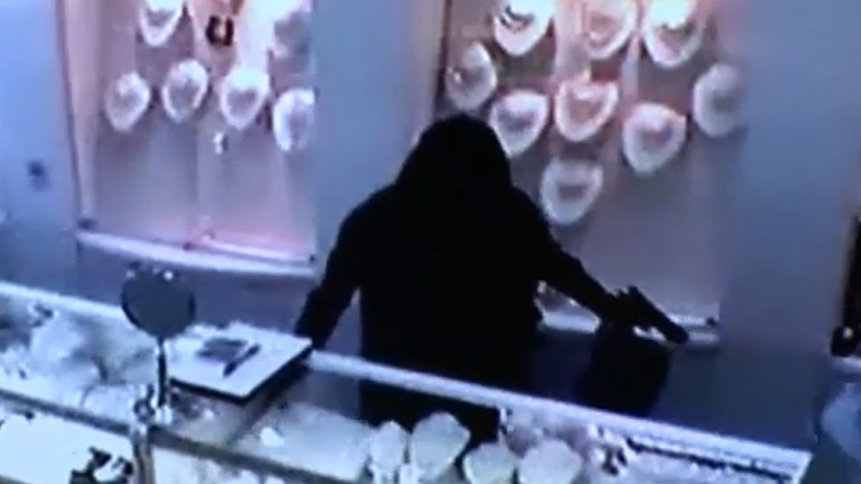 A man is shown robbing Mona-Clara Jewellers in what appears to be a burka in security footage from Tuesday, Oct. 14, 2014. (Toronto Police Service)