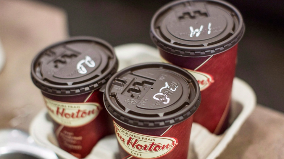 Cups of coffee sit on a counter in a Tim Hortons