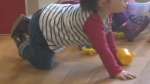A young child crawls along the floor at a childcare centre (file)