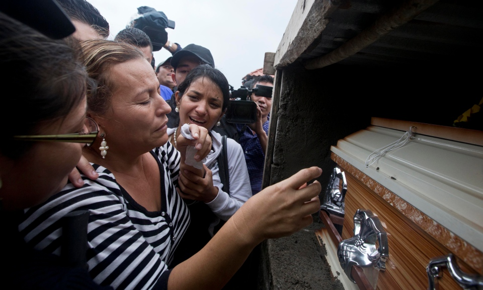 Teresa de Jesus Munoz, the mother of slain beauty queen Maria Jose Alvarado, touches her daughter's coffin during her burial in Santa Barbara, Honduras, Thursday, Nov. 20, 2014. Teresa de Jesus Munoz laid to rest two daughters on Thursday, Maria Jose and Sofia, after the women were shot to death in what police say was a jealous rage by Sofia's boyfriend. (AP Photo/Esteban Felix)