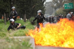 A riot police officer falls after protesters threw molotov cocktails at them near the airport in Mexico City,Thursday, Nov. 20, 2014. (AP / Marco Ugarte)