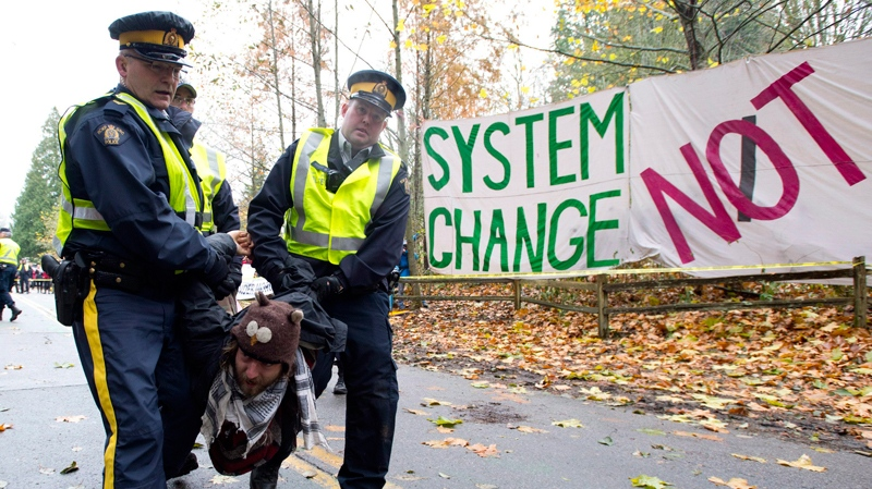 RCMP officers take protesters into custody at an anti-pipeline demonstration in Burnaby, B.C., on Thursday, Nov. 20, 2014. (THE CANADIAN PRESS/Jonathan Hayward)