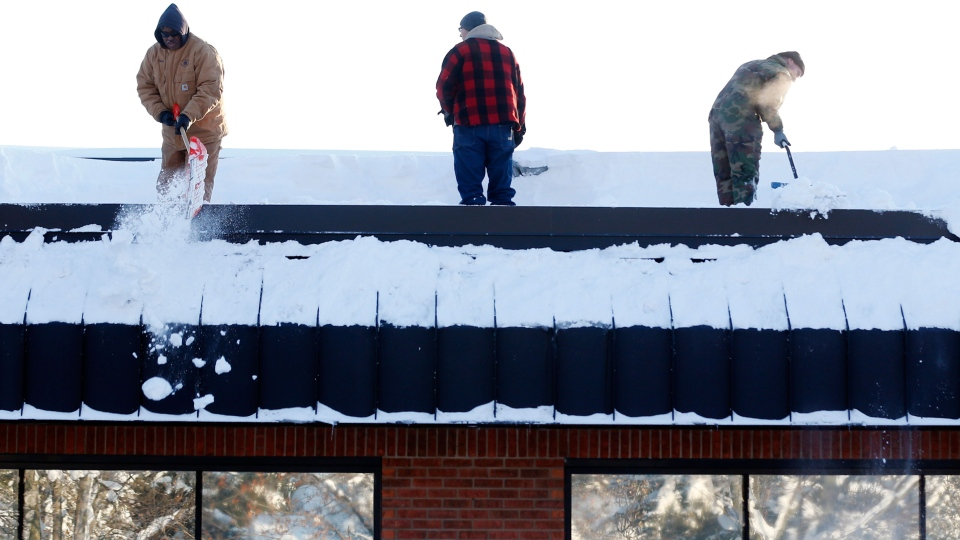 Workers clear snow from the roof of Costanzo's Bakery on Friday, Nov. 21, 2014, in Cheektowaga, N.Y. (AP / Mike Groll)