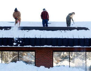 Workers clear snow from the roof of Costanzo's Bakery on Friday, Nov. 21, 2014, in Cheektowaga, N.Y. (AP Photo/Mike Groll)