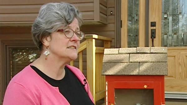 Calgary artist Cheri Macaulay stands next to her 'little library.'