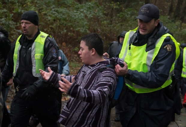 An RCMP officer removes a protester from a road on Burnaby Mountain as Kinder Morgan contractors arrive at the site in preparation for the Trans Mountain Pipeline expansion in Burnaby, B.C., on Friday November 21, 2014. THE CANADIAN PRESS/Darryl Dyck