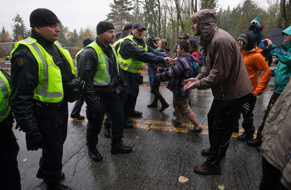 Police and RCMP officers force protesters from a road on Burnaby Mountain as Kinder Morgan contractor vehicles arrive at the site where a borehole is being drilled in preparation for the Trans Mountain Pipeline expansion in Burnaby, B.C., on Friday November 21, 2014. (Darryl Dyck / THE CANADIAN PRESS)