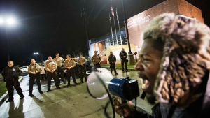 Protester Derrick Robinson shouts through a bullhorn at police officers standing guard during a demonstration outside the Ferguson Police Department in Ferguson, Mo. on Sunday, Nov. 23, 2014. (AP / David Goldman)