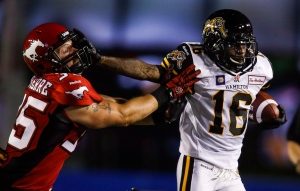 In this file photo, Hamilton Tiger-Cats' Brandon Banks, right, fends off Calgary Stampeders' Tim St. Pierre, during second half CFL football action in Calgary, Alta., Friday, July 18, 2014. (THE CANADIAN PRESS/Jeff McIntosh)