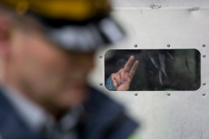 A protester flashes a peace sign from inside a paddy wagon after being taken into custody at an anti-pipeline demonstration in Burnaby, B.C., on Thursday, Nov. 20, 2014. (THE CANADIAN PRESSA/Jonathan Hayward)