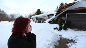 Tami Diestler looks over the exterior of her collapsed home in on Cary Rd. in Alden, NY, Sunday, Nov. 23, 2014. ( Mark Mulville / The Buffalo News)