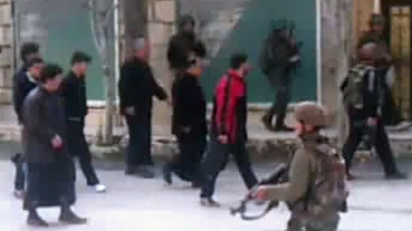 This image made from amateur video and released by Shaam News Network Friday, March 30, 2012, purports to show civilians moving with Syrian troops, possibly as human shields, in Idlib, Syria. (AP / Shaam News Network via AP video)