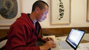 Jamyang Palden, a 30-year-old Tibetan Buddhist monk uses his laptop to access his email at a cafe with WiFi connection in Dharmsala, India, Monday, Nov. 10, 2014. (AP / Ashwini Bhatia)