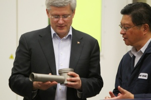 Prime Minister Stephen Harper and employee Lee Xiu look over devices fabricated on 3-D printers at The National Research Council building in London, Ont., on Monday, Nov. 24, 2014. (Dave Chidley / THE CANADIAN PRESS)