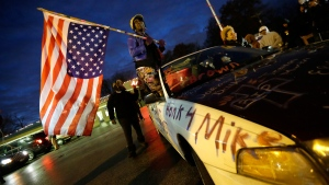 Gina Gowdy holds an upside-down American flag, in Ferguson, Mo., Monday, Nov. 24, 2014. (AP / Charlie Riedel)