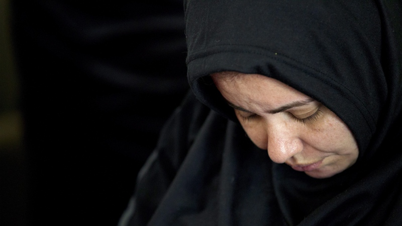 A woman bows her head during a memorial for Shaima Alawadi at a mosque Tuesday, March 27, 2012, in Lakeside, Calif. The body of Alawadi, who grew up in Iraq and wore the Muslim headscarf, was found severely beaten in her suburban San Diego home on March 21.