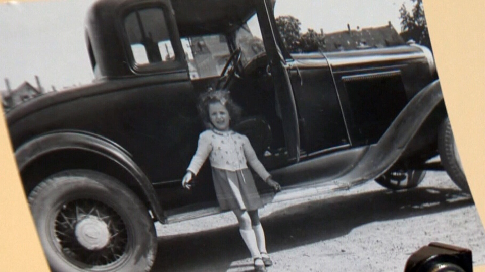 Mysterious development: an unidentified girl poses beside a vintage car