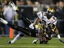 Hamilton Tiger-Cats' Scott Mitchell, bottom, makes a touch down catch as Winnipeg Blue Bombers Jovon Johnson tries to block the pass during first half CFL action on Friday, Sept. 19, 2008 in Hamilton, Ontario. THE CANADIAN PRESS/Nathan Denette