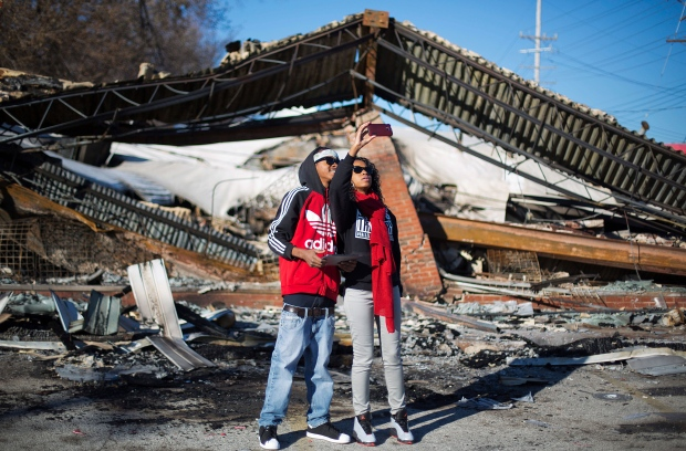 Darius Crenshaw, left, and his sister Keona, both of Ferguson, Mo., take a selfie while standing in front of a burned down beauty salon from last night's riots, Tuesday, Nov. 25, 2014, in Ferguson, Mo. (AP / David Goldman)