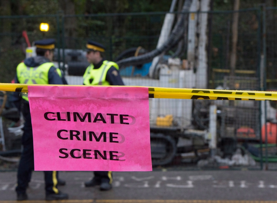 RCMP are pictured in the background protecting a Kinder Morgan drill as a sign placed by a anti-pipeline demonstrator is pictured in the foreground in Burnaby, B.C., on Monday, Nov. 24, 2014. (Jonathan Hayward / THE CANADIAN PRESS)