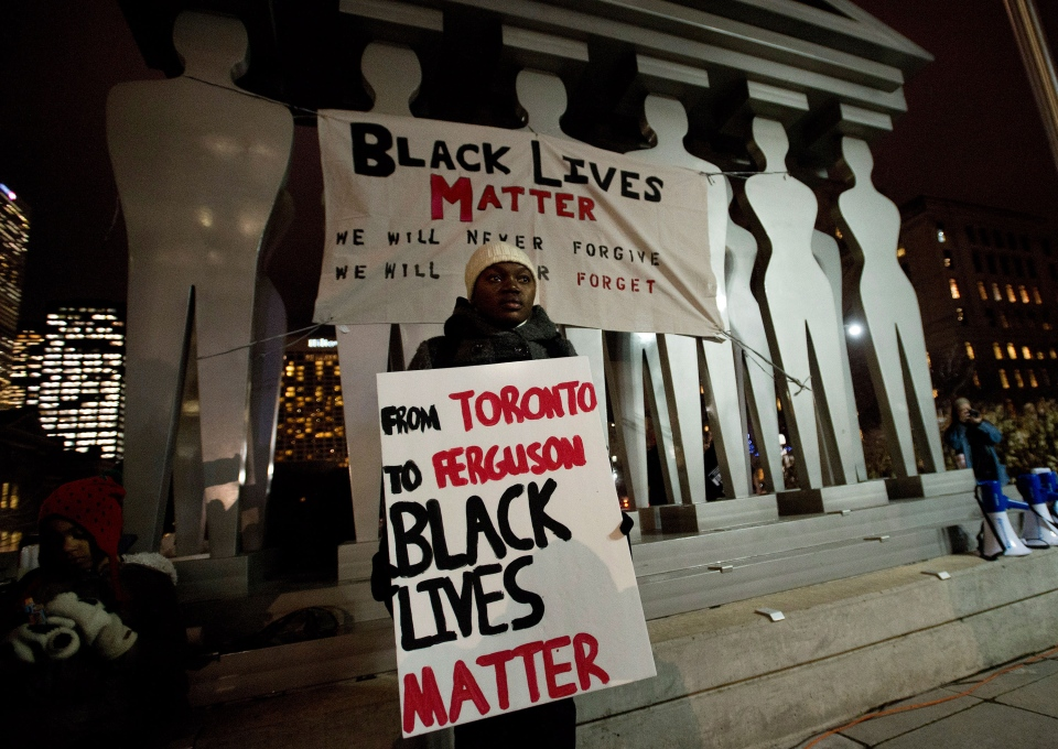People protest a United States grand jury's decision not to indict a police officer who shot and killed Michael Brown of Feguson, Mo., outside the U.S. Consulate in Toronto on Tuesday, Nov. 25, 2014. (Nathan Denette / THE CANADIAN PRESS)