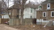 Winnipeg police are investigating a murder after a man was found lying dead in the yard between these two homes on Balmoral Street.