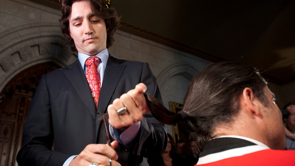Liberal MP Justin Trudeau trims the end of Conservative Senator Patrick Brazeau's pony tail out of respect in the Foyer of the House of Commons on Parliament Hill Ottawa, Monday April 2, 2012. (THE CANADIAN PRESS/Adrian Wyld)