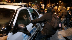 Protesters vandalize a police vehicle near Ferguson City Hall, in Ferguson, Mo. Tuesday, Nov. 25, 2014. (AP / David Goldman)