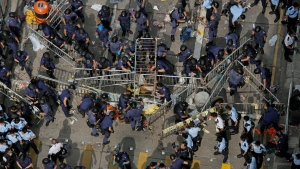 Police officers clear a metal barricades while others tear down tents and canopies and carry away other obstructions after bailiffs issued a warning to the crowd that they would start enforcing the court-ordered clearance at an occupied area in Mong Kok district of Hong Kong Wednesday, Nov. 26, 2014. (AP / Vincent Yu)