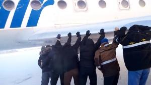 Canada AM: Passengers push plane on to runway