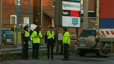 Police officers monitor a Toronto gas station that is dropping its price to 50 cents per litre on Monday, April 2, 2012.