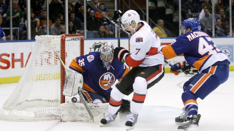 New York Islanders' Al Montoya, left, defends the net while teammate Andrew MacDonald, right, and Ottawa Senators' Kyle Turris skate by during the first period of the NHL hockey game on Sunday, April 1, 2012, in Uniondale, N.Y. (AP Photo/Seth Wenig)