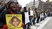 Demonstrators block Public Square Tuesday, Nov. 25, 2014, n Cleveland, during a protest over the weekend police shooting of Tamir Rice. The 12-year-old was fatally shot by a Cleveland police officer Saturday after he reportedly pulled a replica gun at the city park. (AP Photo/Tony Dejak)