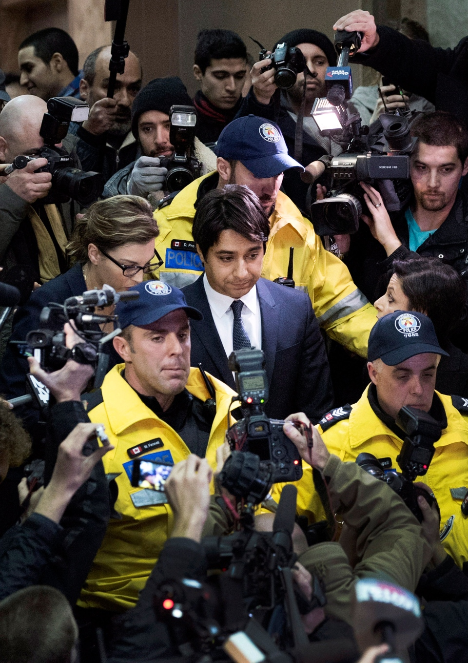 Jian Ghomeshi makes his way through a mob of media at a Toronto court Wednesday, Nov. 26, 2014. (Darren Calabrese / THE CANADIAN PRESS)