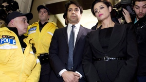 Police try to clear a path as Jian Ghomeshi makes his way through a mob of media with his lawyer Marie Henein (right) at a Toronto court, Wednesday, Nov. 26, 2014. (Nathan Denette  / THE CANADIAN PRESS)