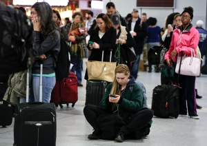 Thanksgiving holiday travellers wait for departure announcements at Penn Station in New York, Wednesday, Nov. 26, 2014. (AP / Julie Jacobson)