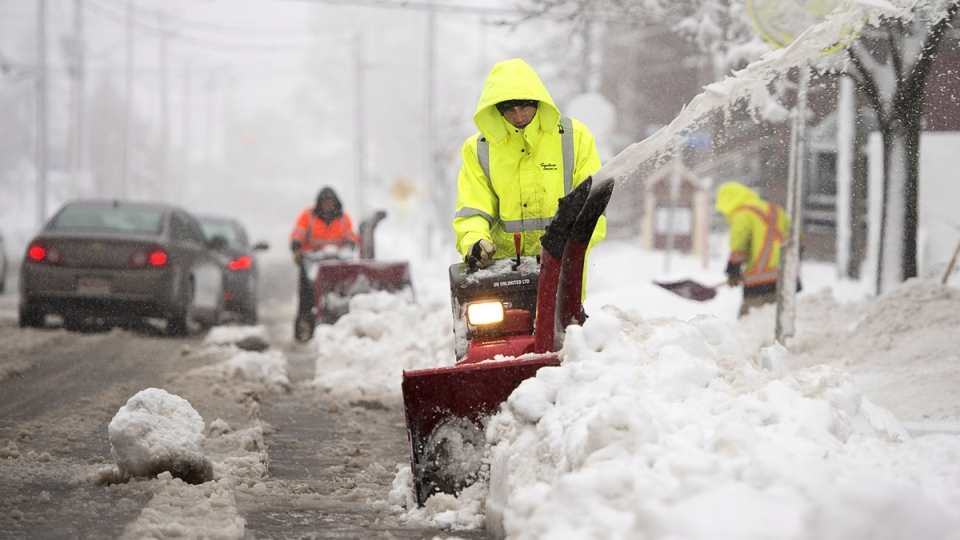Workers clear sidewalks in Moncton, N.B. on Thursday, Nov. 27, 2014. (Andrew Vaughan / THE CANADIAN PRESS)