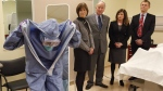 Judith Bosse (left to right), Assistant Deputy Minister at the Public Health Agency of Canada, Defence Minister Rob Nicholson, Health Minister Rona Ambrose and Dr. Gregory Taylor, Canada's Chief Public Health Officer, watch as nurse Adina Popalyar demonstrates how to remove protective clothing after treating a hypothetical Ebola patient at the Ottawa Hospital Research Institute, Thursday, Nov. 27, 2014. (Patrick Doyle / THE CANADIAN PRESS)