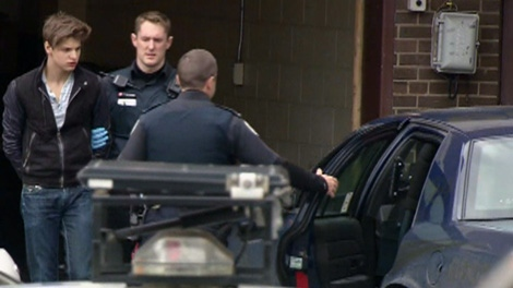 Oliver Karafa, 19, is seen being taken into custody by police, Tuesday, April 3, 2012.