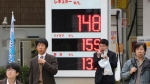 People wait to cross a street in front of a Shell filling station in Tokyo on Nov. 28, 2014. A renewed plunge in oil prices is a worrying sign of weakness in the global economy (AP / Koji Sasahara)