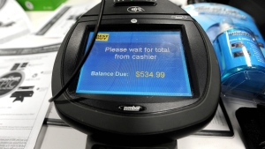 Credit card machines were busy as bargain hunters at Best Buy make doorbuster purchases just after midnight on Black Friday. (AP / David Tulis)